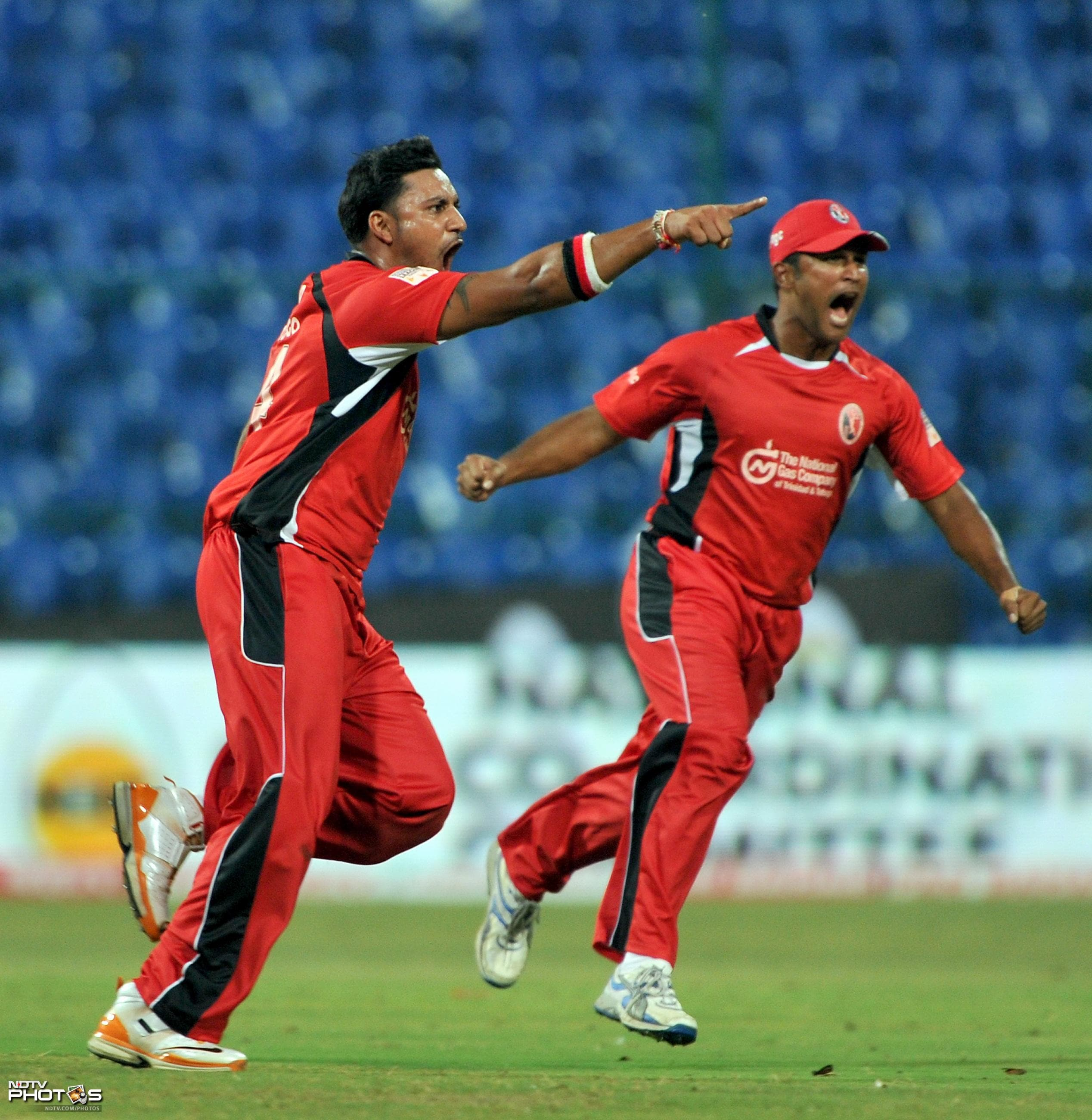 Ravi Rampaul and Darren Ganga celebrate the dismissal of Andrew Symonds during the Champions League Twenty20 League Group A match between Mumbai Indians and Trinidad and Tobago at the M. Chinnaswamy Stadium in Bangalore. (AFP Photo)