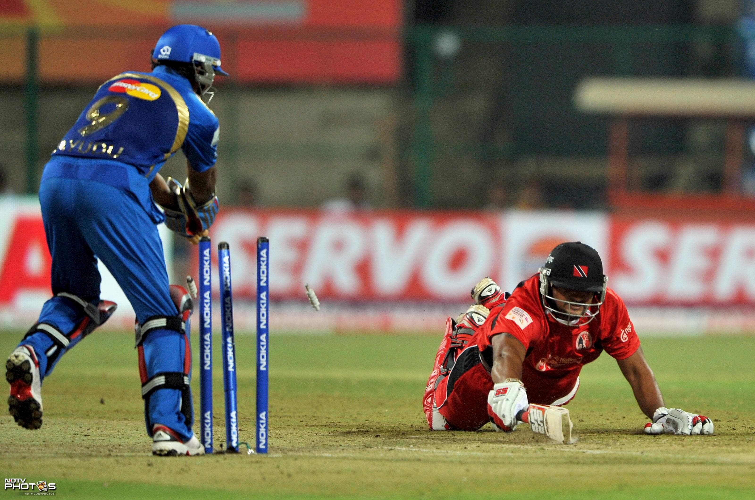 Ravindranath Rampaul makes a vain attempt to reach the crease while being stumped out by wicketkeeper Ambati Rayudu during the Champions League Twenty20 cricket Group A match between Mumbai Indians and Trinidad and Tobago at the M. Chinnaswamy Stadium in Bangalore. (AFP Photo)