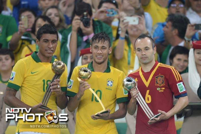 Paulinho, Neymar and Iniesta pose with their Bronze, Silver and Golden Ball trophies respectively as they finish at the top of the goal scorers in the competition.