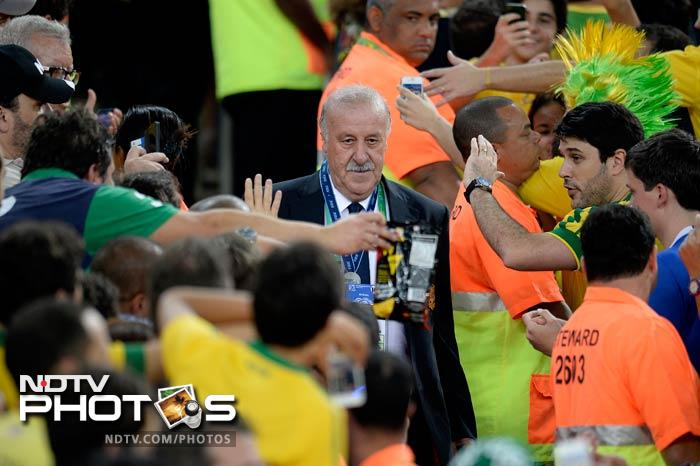 Spain coach Vicente Del Bosque walks with a grim face through the throng of Brazilian supporters.