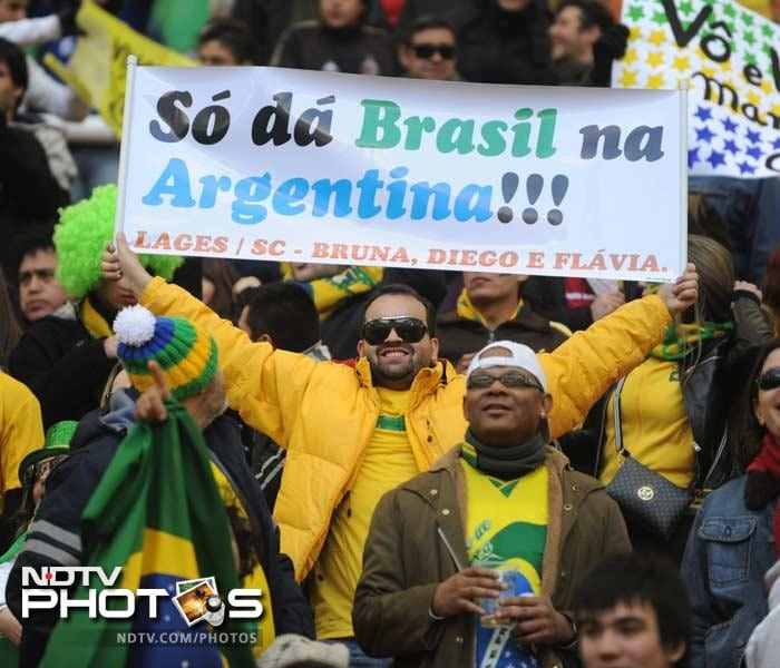 Verbal affection can turn into friendly intimidation as a Brazilian fan this time, holds a banner which says (translating roughly) that Brazil will down Argentina.
