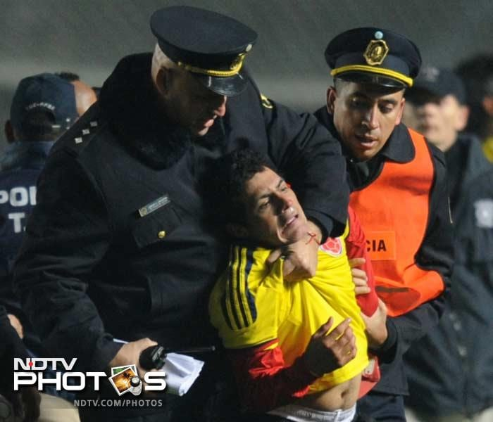 Silence is not a virtue that this fan has as he grimaces after being arrested for entering the field of play during a match between Colombia and Argentina. While nothing new, passions have engulfed fans in no small measure.