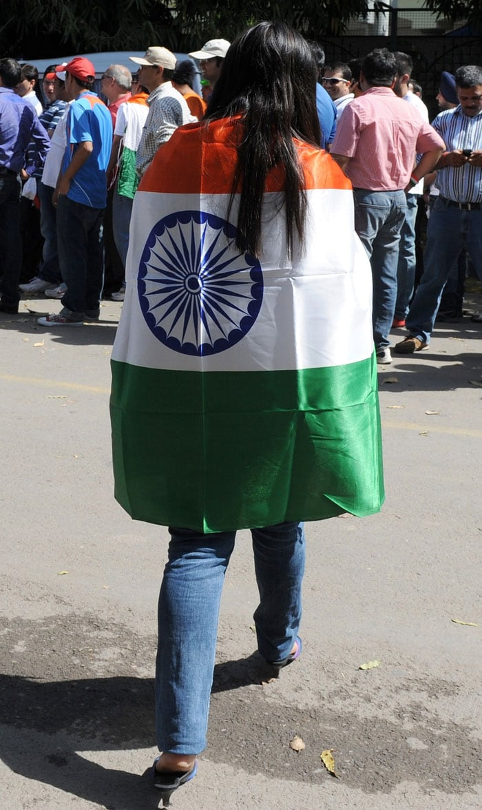 View from the back: A woman roots for India with the tricolor swathed over her.