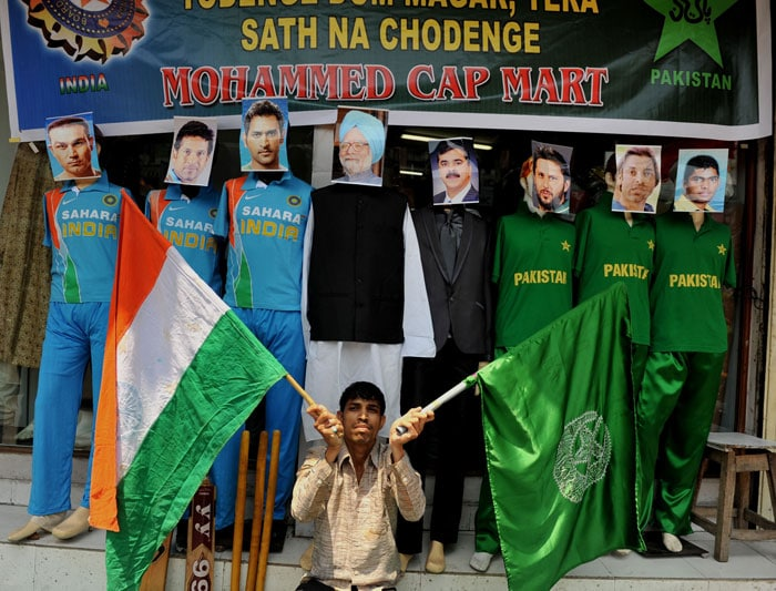 Man in the middle: A fan poses with cutouts of the Ind-Pak teams with Prime Minister Manmohan Singh's cutout in the centre.