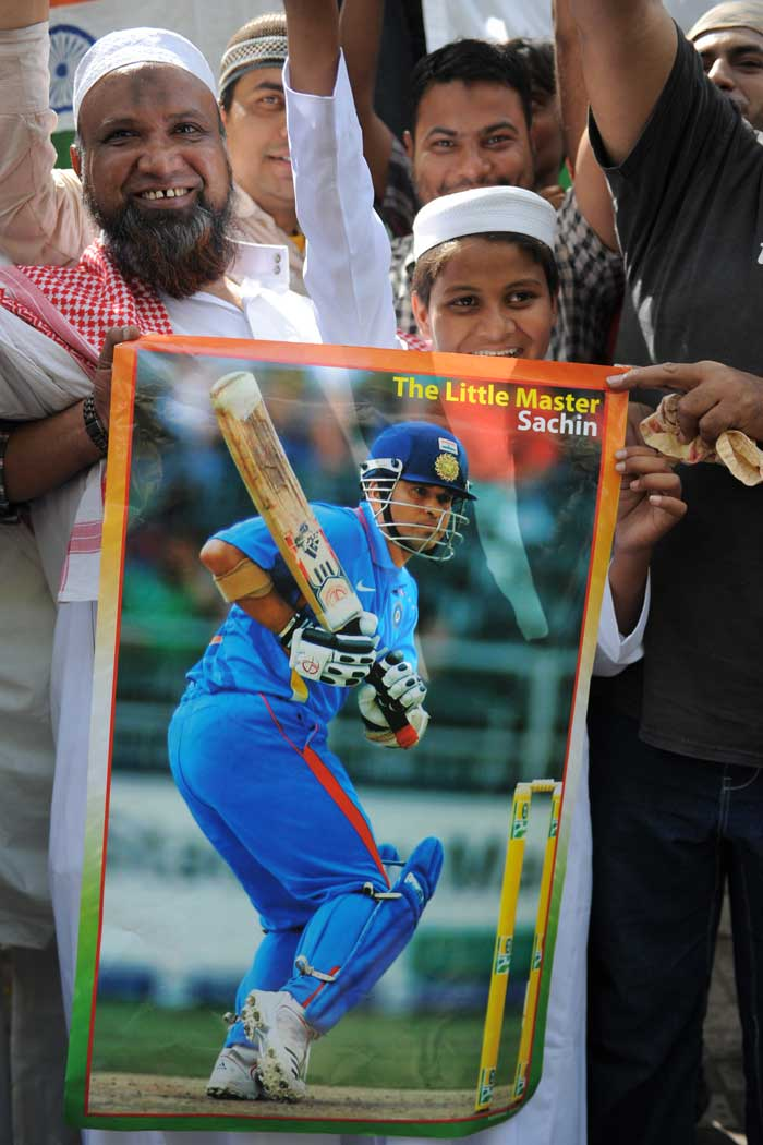 Fans wave a poster of Sachin Tendulkar at the Siddi Saiyed Jaali Mosque in Ahemedabad.(Image courtesy: AFP)