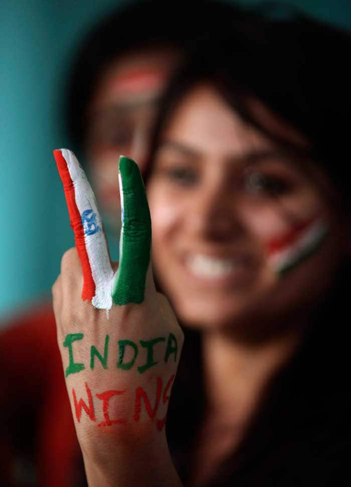 Painted faces and hands: A fan proves her patriotism by painting the Indian flag.