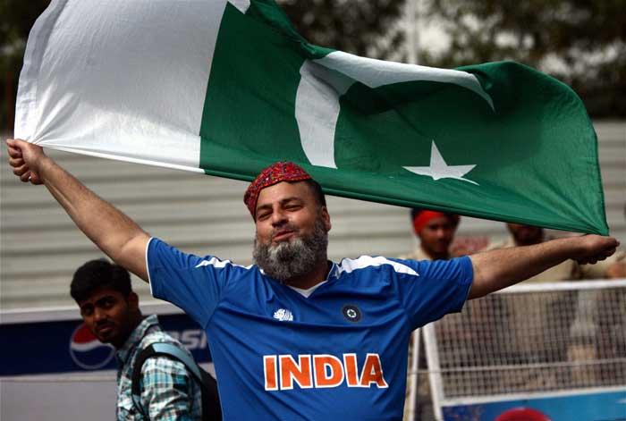 A Pakistani fan, wearing an Indian t-shirt, raises slogans for peace.