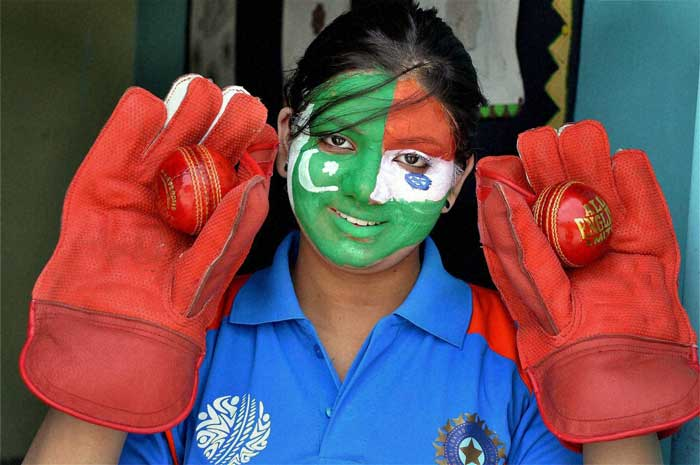 A girl paints her face with flags from India and Pakistan.