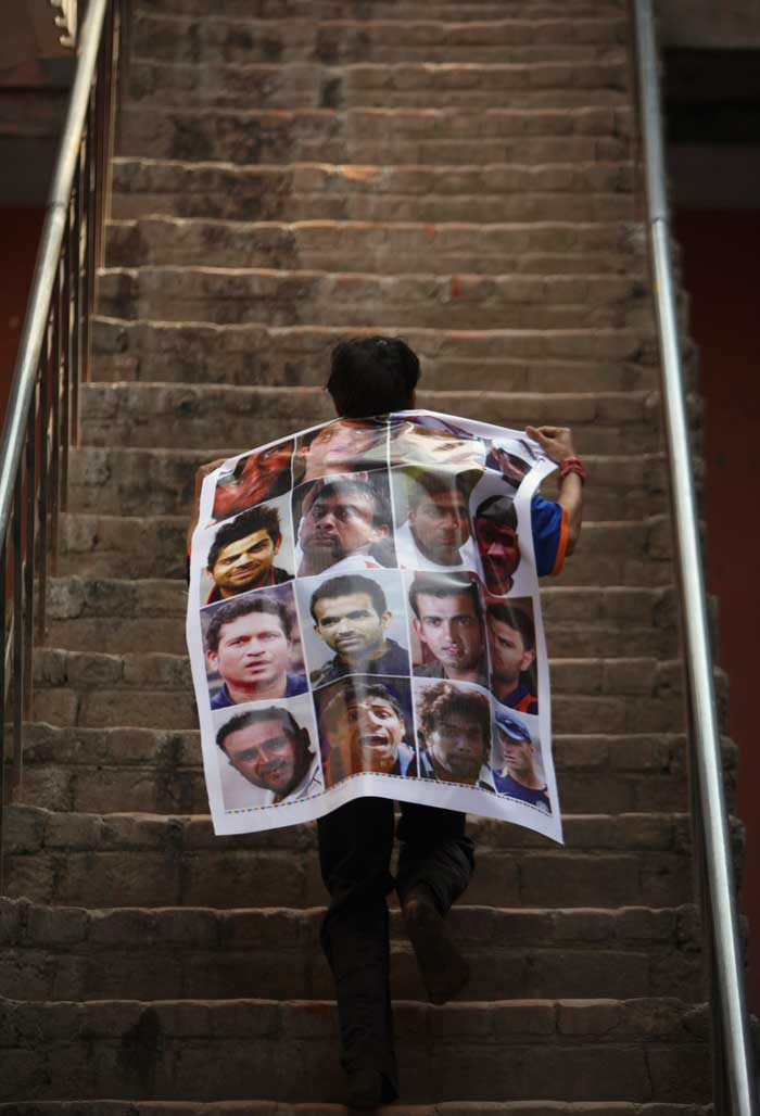 A young boy shows his craze for the sport and carries a collage of photographs of the Indian cricket team.