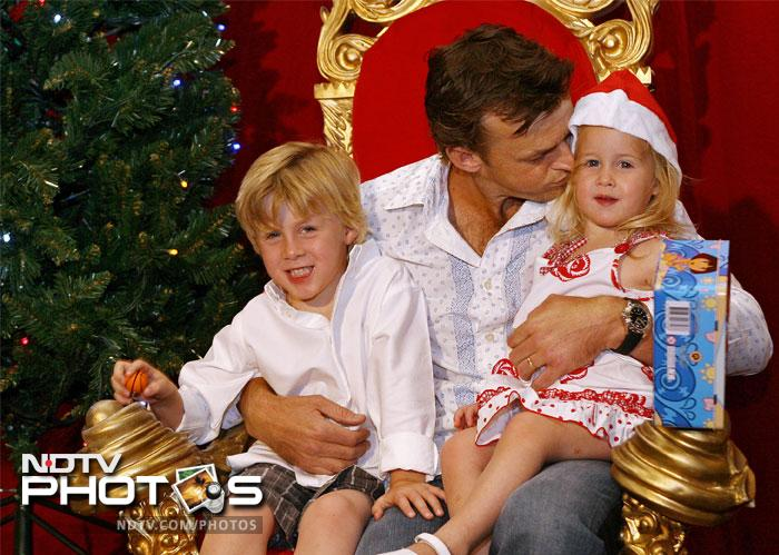 Adam Gilchrist (C) embraces his children Harry (L) and Annie (R) at a Christmas party in 2006.