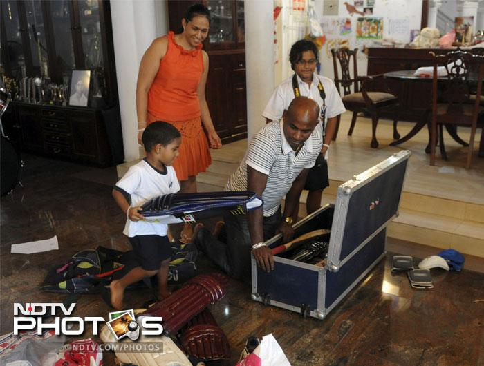 Sri Lankan cricketer Sanath Jayasuriya (C) gets some help from his son Ranuk (L) as he packs his cricket gear. Wife Samadra (2L), and daughter Kashini (R) look on. (June, 2011).