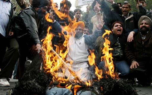Indian cricket supporters stand beneath a burning effigy as they stage a protest in Amritsar