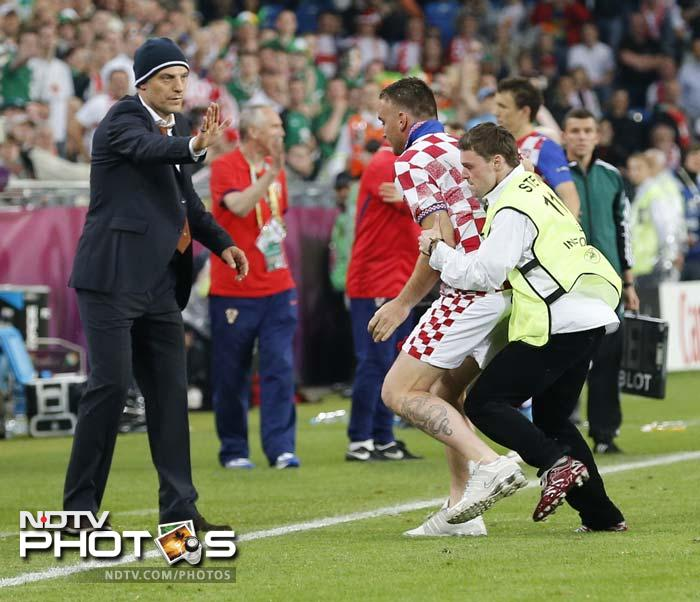 A steward takes a man who got onto the pitch as Croatia head coach Slaven Bilic looks on during the match.