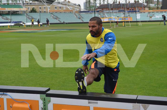 Dhawan does a stretch to loosen up during the training session.