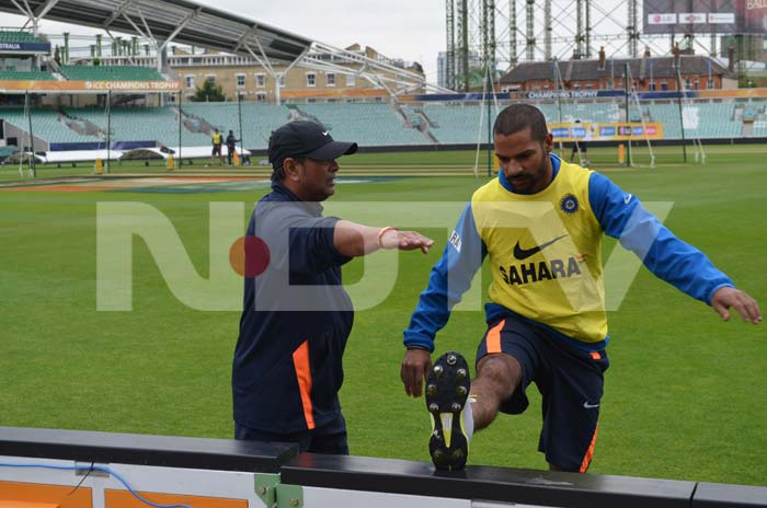 A team instructor gives Dhawan tips to exercise as the team trains at The Oval.