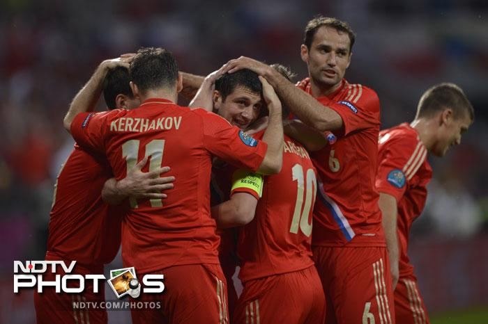 Alan Dzagoev's brace helped Russia dismantle Czech Republic 4-1. Here the Russian midfielder (C) is seen being congratulated by his teammates after scoring the first goal during the Euro 2012 football match. (AFP PHOTO / FABRICE COFFRINI)