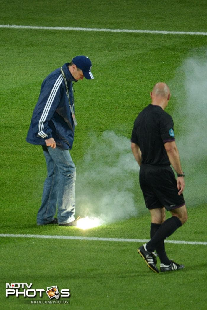 Czech Republic looked down and out while the Russian 'fire' was unstoppable. Referee Howard Webb looks on as an employee tries to extinguish a flare. (AFP PHOTO / FRANCISCO LEONG)