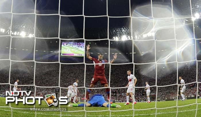 Polish goalkeeper Przemyslaw Tyton (down) makes a save in front of Czech forward Milan Baros during the Euro 2012 championship football match in Wroclaw.