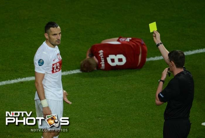 Polish defender Marcin Wasilewski (L) is given a yellow card by the referee during the Euro 2012 championships football match against the Czech Republic in Wroclaw.