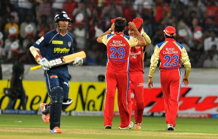 The Royal Challengers Bangalore team celebrates the wicket of Deccan Chargers captain Kumar sangakkara (L) during the IPL twenty 20 match at the Rajiv Gandhi International Stadium in Hyderabad. (AFP PHOTO)