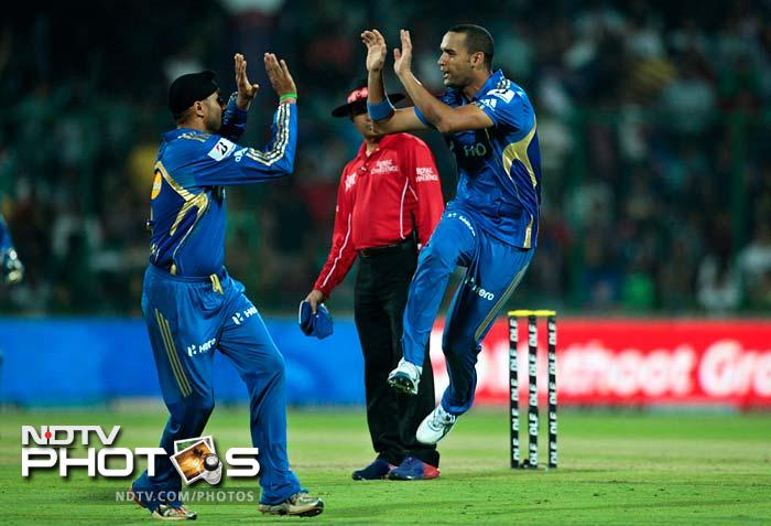 Robin Peterson of Mumbai Indians, right, celebrates with Harbhajan Singh, after claiming the wicket of Irfan Pathan against Delhi Daredevils during their IPL cricket match in New Delhi. (AP Photo/Saurabh Das)