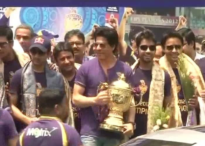King Khan holds the trophy as Gautam Gambhir and other players look on.