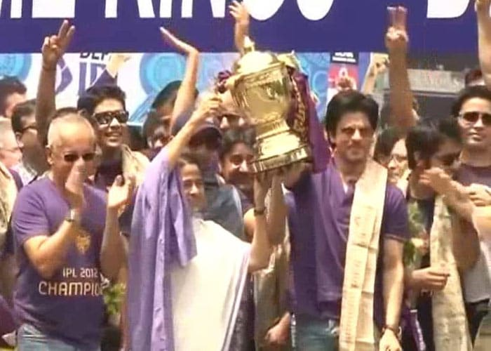 Chief Minister Mamata Banerjee lifts the IPL trophy as Shah Rukh Khan looks on.