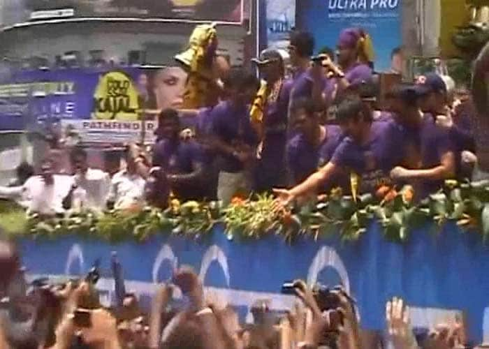 Kolkata players, atop the rally trailer, greet the supporters amidst massive celebrations.