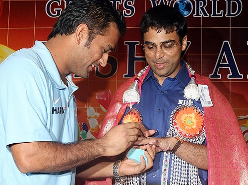MS Dhoni gives a one-carat diamond ring to World Chess Champion Viswanathan Anand on his birthday at a function to felicitate him, in Chennai on December 11, 2008. (AFP Photo)