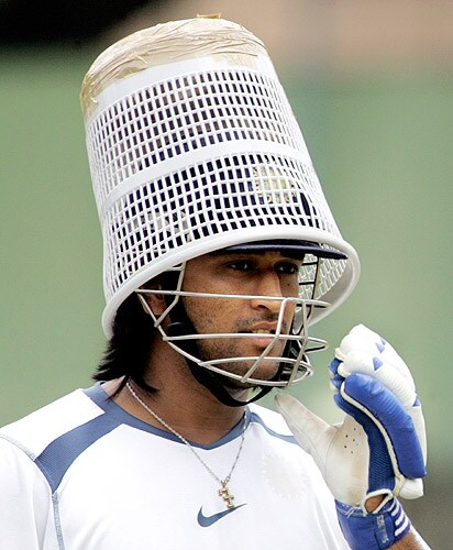 MS Dhoni puts a basket on his head during a practice session at the National Cricket Academy (NCA) in Bangalore on September 04, 2006. (AFP Photo)