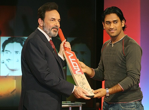 MS Dhoni hands over a signed bat to New Delhi Television (NDTV) President and Chairman Prannoy Roy during a press conference, in New Delhi on May 07, 2006. NDTV signed a contract with Dhoni for a period of one year starting 07 may 2006, during which he was available exclusively on NDTV for all interviews, views and special shows. (AFP Photo)