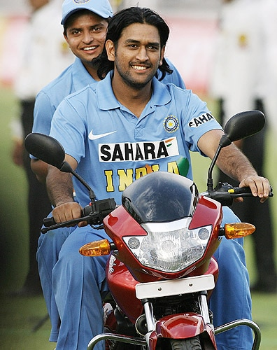 MS Dhoni drives the prize bike with 'Man of the Match' Suresh Raina after victory against England during the second ODI match between India and England at The Nahar Singh Cricket Ground in Faridabad on March 31, 2006. (AFP Photo)