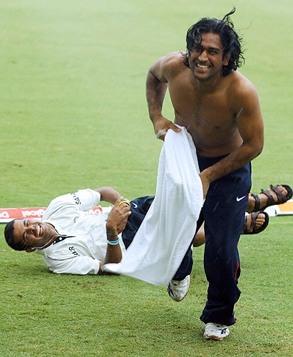 MS Dhoni runs back to the shelter of the dressing room after pushing out teammate S Sreesanth in the rain at the ground as start of play was delayed by rain on the fourth day of the second Test between India and the West Indies at the Beausejour Stadium in Gros Islet, St Lucia on June 13, 2006. (AFP Photo)