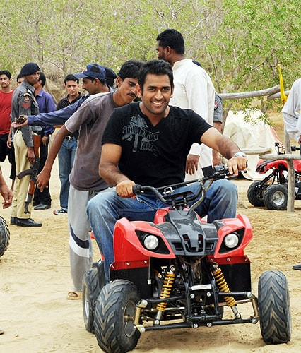 Indian team captain Mahendra Singh Dhoni drives a motor cart at a resort in Karachi on June 29, 2008. (AFP Photo)