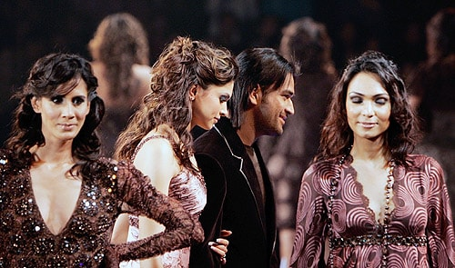 MS Dhoni walks with models as he presents the creations of Indian designers Rohit Gandhi-Rahul Khanna's Cuein in New Delhi on November 10, 2006. (AFP Photo)