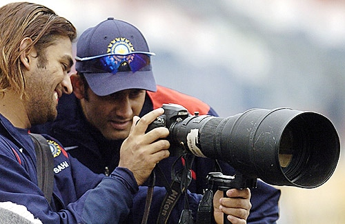 Anil Kumble and MS Dhoni view the photographs on a camera during a practice session before the start of the fourth day of the first Test match between Pakistan and India at The Gaddafi Cricket Stadium in Lahore on January 16, 2006. (AFP Photo)