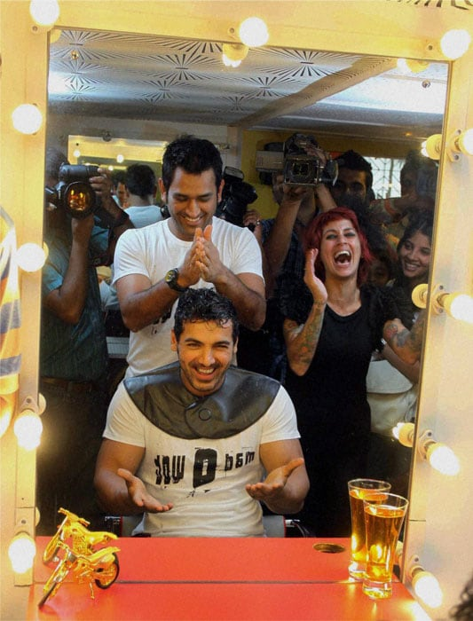 Bollywood meets cricket once again. Actor John Abraham and Team India skipper MS Dhoni were at the Mad-O-Wat salon in suburban Bandra where they styled each other's hair. (PTI Photo)