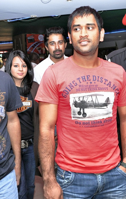 Captain of the Indian cricket team MS Dhoni alongwith his wife Sakshi outside a multiplex in Ahmedabad to watch Action Replayy. The Indian team was in the city to play a Test match against New Zealand. (PTI Photo)