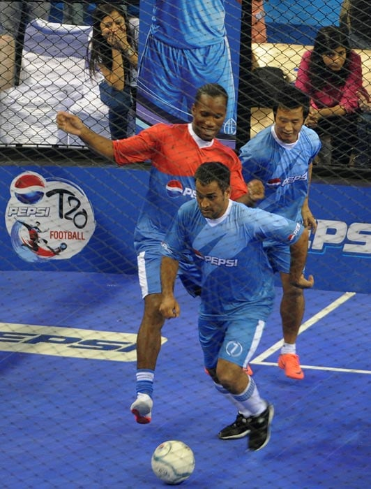 Indian cricket team captain MS Dhoni tries to get the ball past International football player from the Ivory Coast Didier Drogba and former India football captain Bhaichung Bhutia during their exhibition match in New Delhi. (AFP Photo)