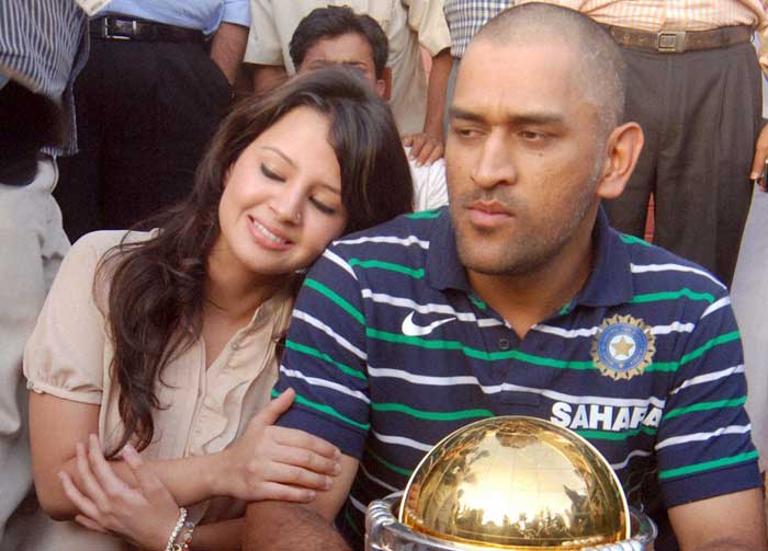 World Cup winning captain Mahendra Singh Dhoni with the World Cup trophy alongside wife Sakshi. (PTI Photo)