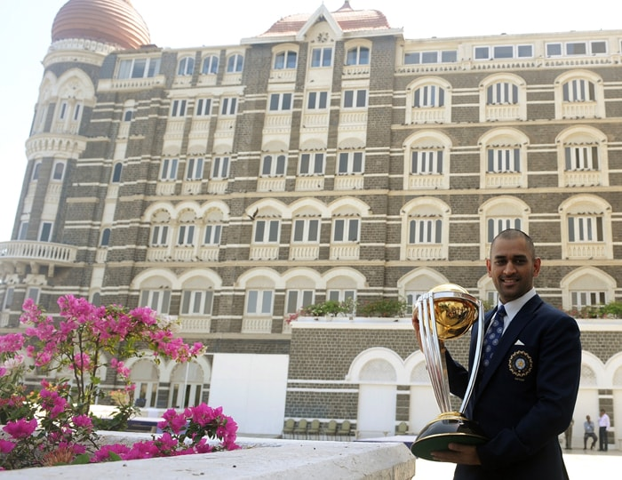 Mahendra Singh Dhoni poses with the ICC Cricket World Cup trophy during a photo call at the Taj Mahal hotel in Mumbai. (AFP Photo)