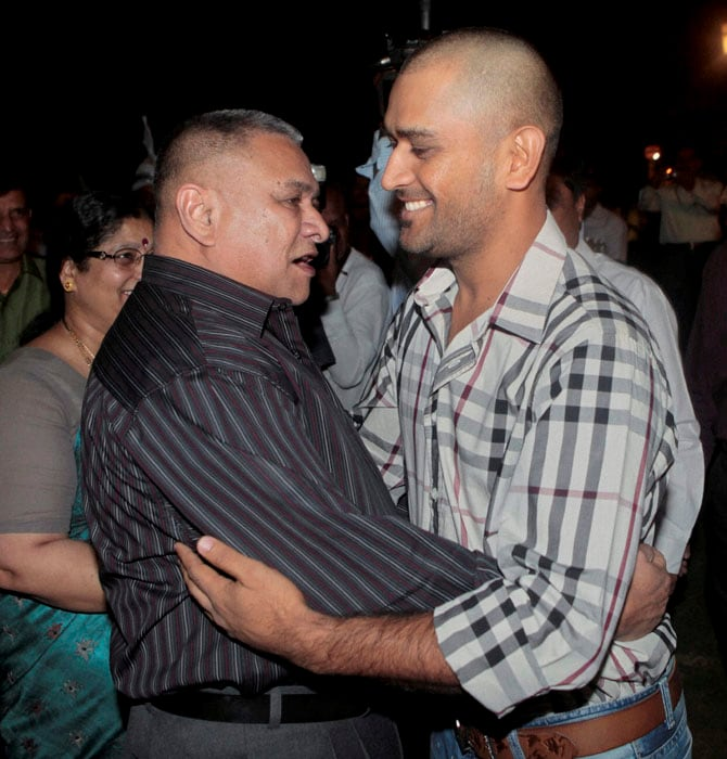 Air Chief Marshal PV Naik hugs World Cup winning Indian team captain M S Dhoni at the former's residence in New Delhi on Monday. (PTI Photo)