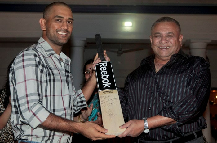 Air Chief Marshal PV Naik is gifted with a bat by World Cup winning Indian team captain M S Dhoni at the former's residence in New Delhi. (PTI Photo)