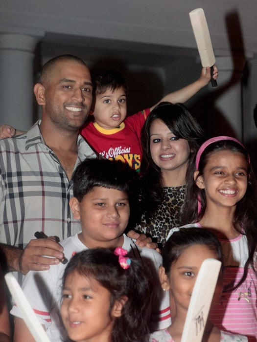 World Cup winning Indian team captain M S Dhoni and his wife Sakshi pose for a photo with kids during a meeting with Indian Air Force chief PV Naik in New Delhi. (PTI Photo)