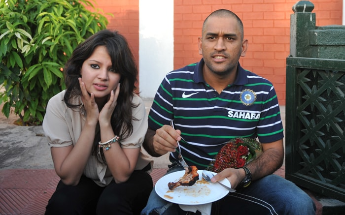 Mahendra Singh Dhoni in his new look with wife Sakshi. (PTI Photo)