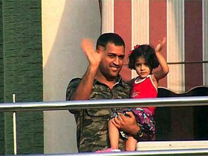 Dhoni holds his niece in his arms at his residence in Harmu, Ranchi. (PTI Photo)