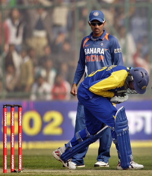 Dinesh Karthik looks on as Tillakaratne Dilshan reacts in pain after he was hit by a ball from India's Ashish Nehra during the fifth and final ODI between India and Sri Lanka in New Delhi. (AP Photo)