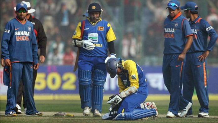 Tillakaratne Dilshan holds his hand after he was hit during the final match between India and Sri Lanka at Ferozshah Kotla stadium in New Delhi. (PTI Photo)