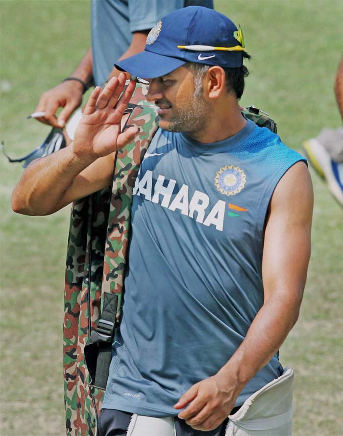India skipper Mahendra Singh Dhoni waves to someone on the field as he warms up for the first Test against West Indies starting Wednesday at the Eden Gardens, Kolkata.