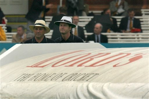 Umpires Simon Taufel, right, and Mark Benson walk to the wicket as the cover is removed at the start of the fourth one-day international between England and South Africa at Lord's cricket ground on Sunday Aug 31, 2008.